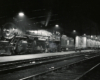 A steam locomotive and passenger train idle under platform lights next to a passenger platform at night.