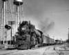 A large steam locomotive leads a freight train beside water towers under clear skies.