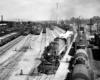A steam locomotive hauling a freight train out of a rail yard.