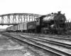 An older steam locomotive leads an express train underneath an arched girder bridge.