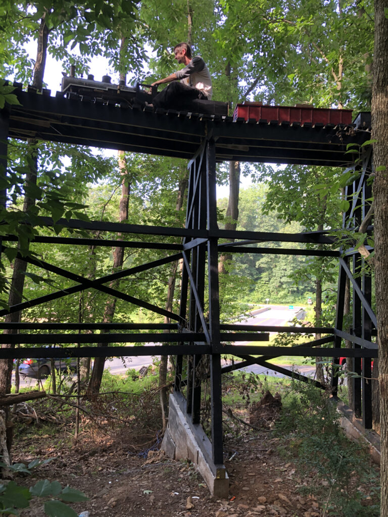 Man on a ride-on train over a trestle