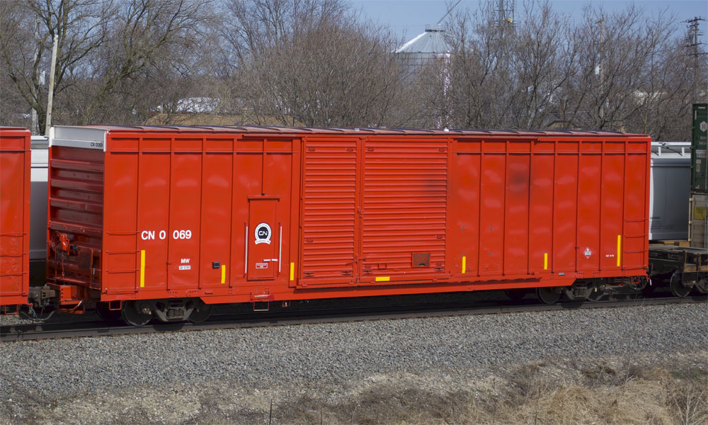 A bright red-orange Canadian National boxcar is seen in the middle of a freight train.