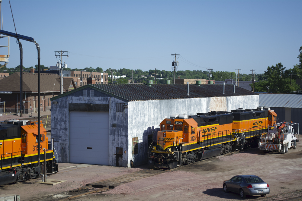 Metal enginehouse with worn white and green paint and two BNSF Ry. road locomotives parked next to it.