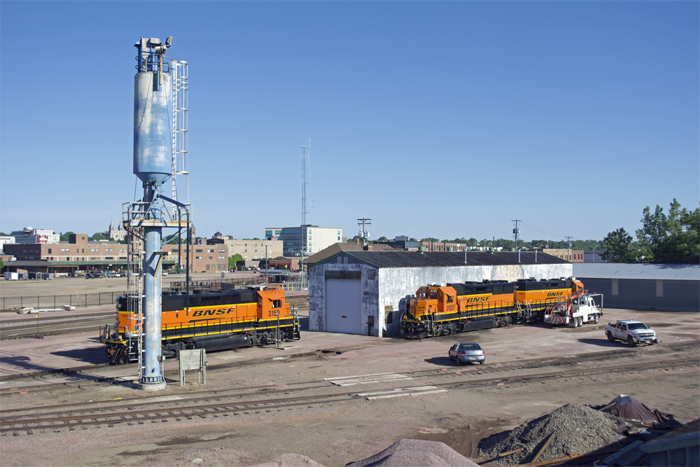 Metal enginehouse and sand tower with three BNSF Ry. road locomotives parked by building.