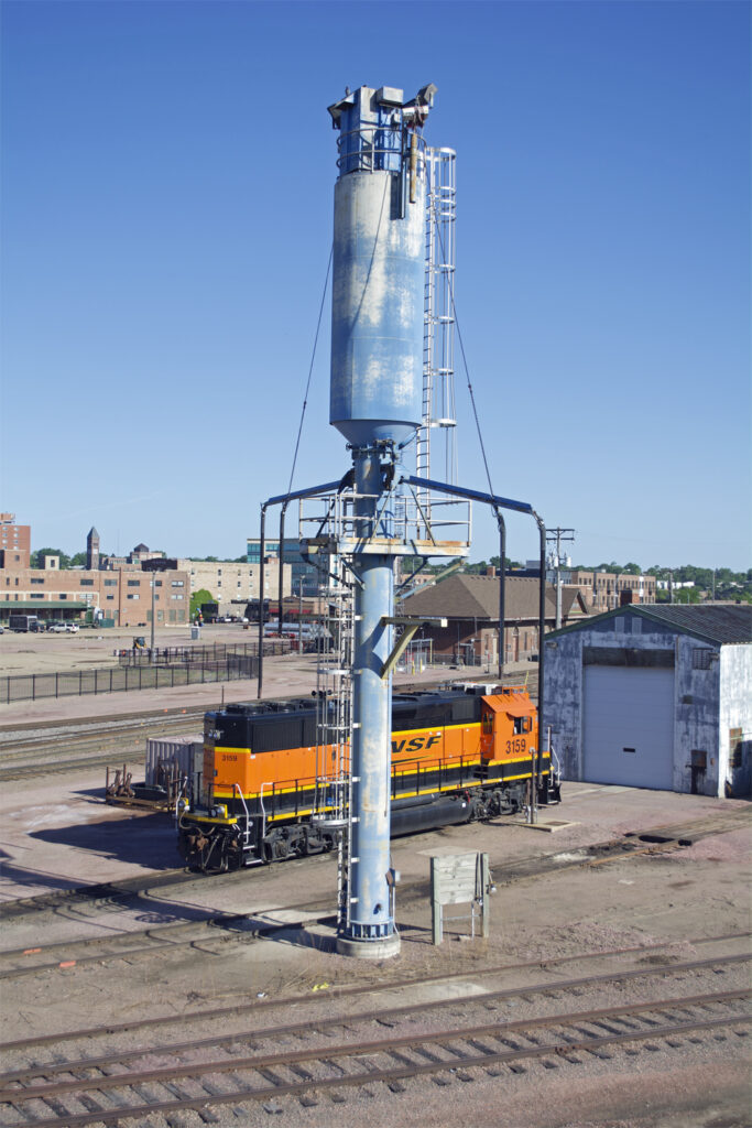 Blue two-track sanding tower with BNSF Ry. road locomotive in background.