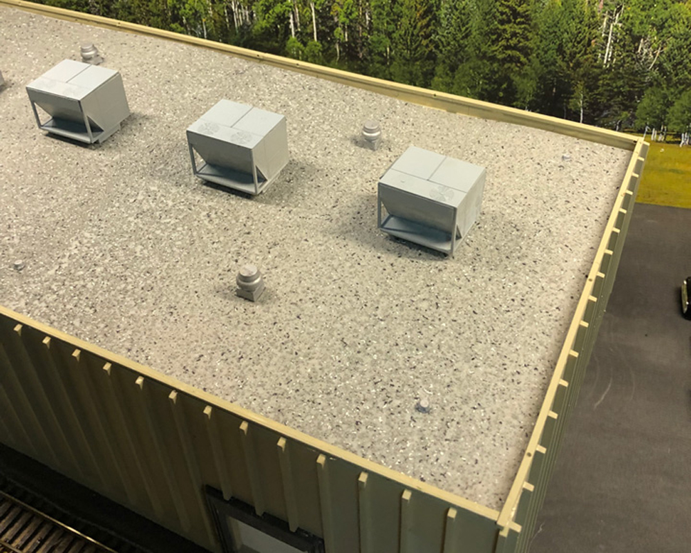 A model of a concrete building features a flat roof with a painted gravel texture.