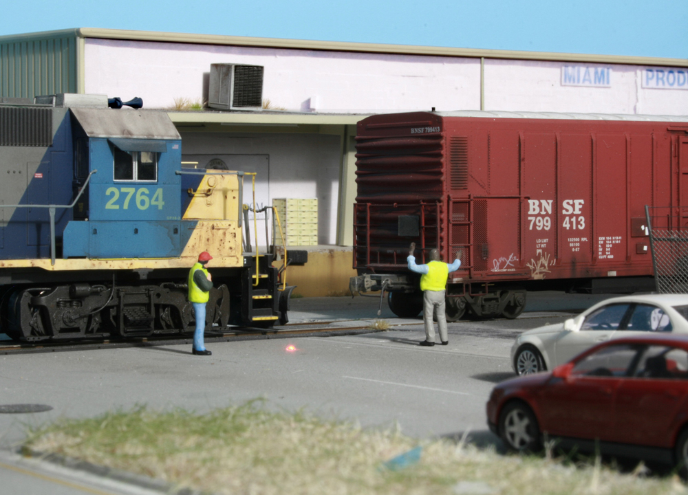 Two model figures next to two model trains