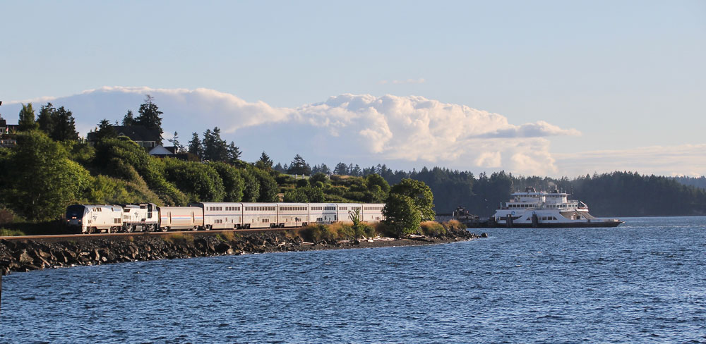 passenger train next to shoreline with ferry
