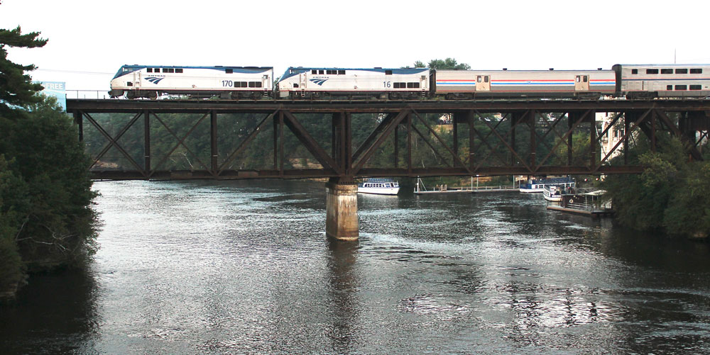 passenger train on bridge over lake with boats beneath