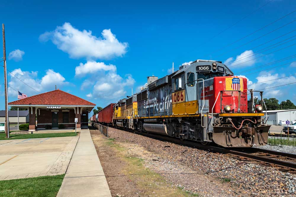 Gray and red diesel locomotive pulls train past brick and red tile roof depot