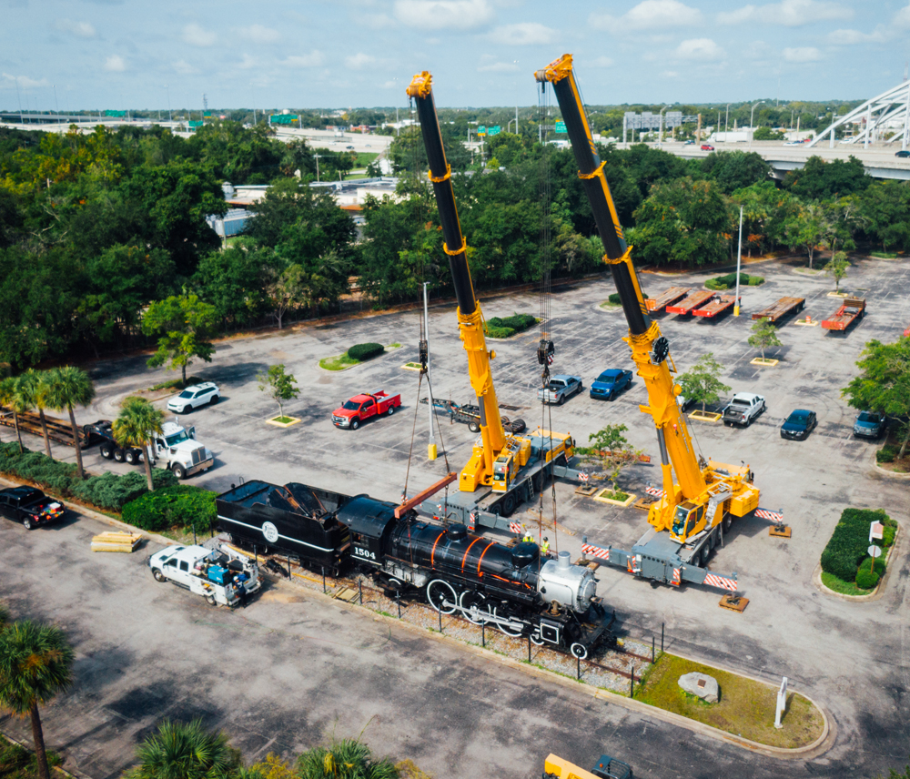 Cranes and steam locomotive in parking lot