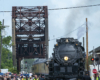 A crowd of people get close to a large steam locomotive that is stopped near an old truss bridge.
