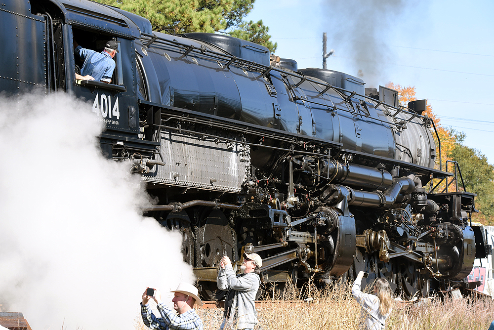 Photographers stand in a ditch alongside steam locomotive