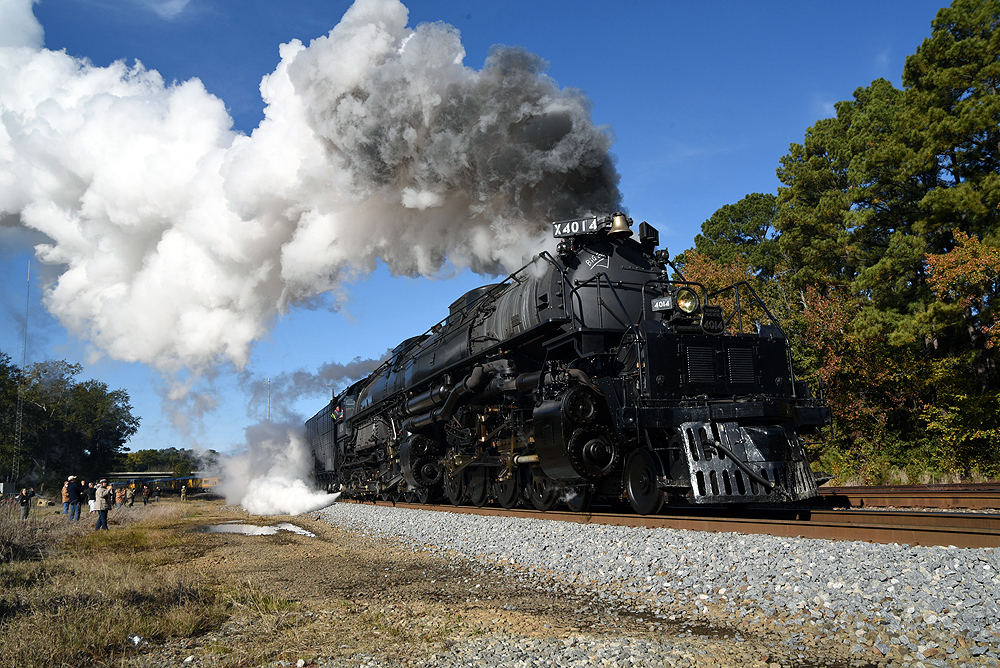Steam locomotive smokes profusely among trees