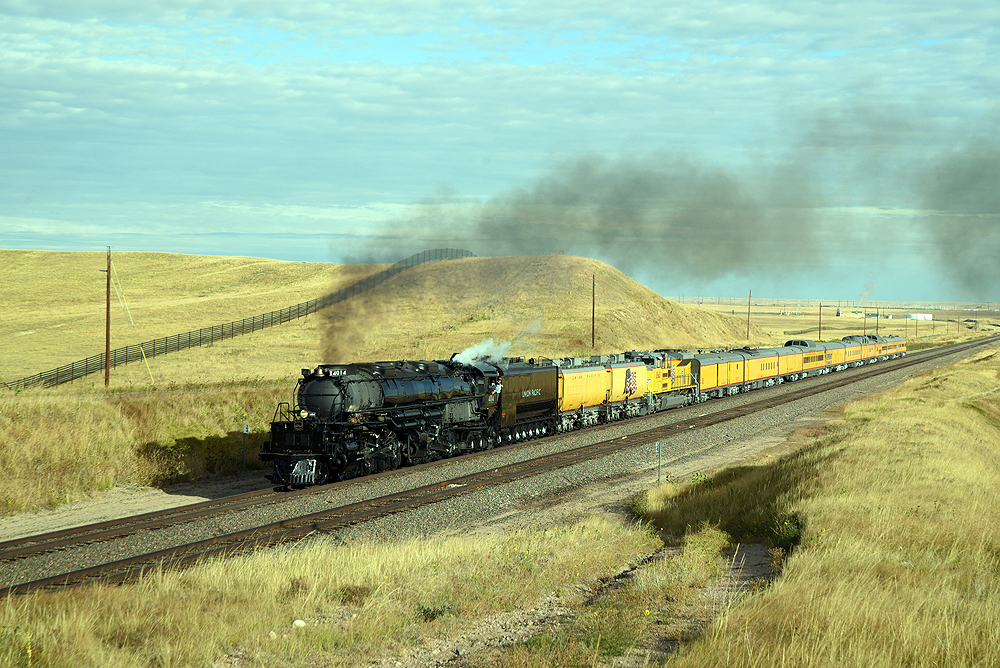 Steam locomotive with yellow passenger train in rolling hills