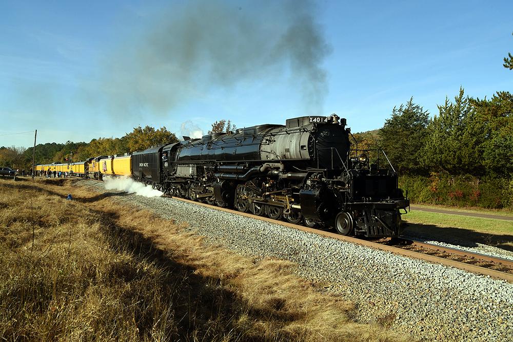 Steam locomotive smoking lightly with yellow passenger train