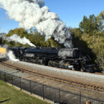 Fence separates spectators from steaming and smoking steam locomotive on curve