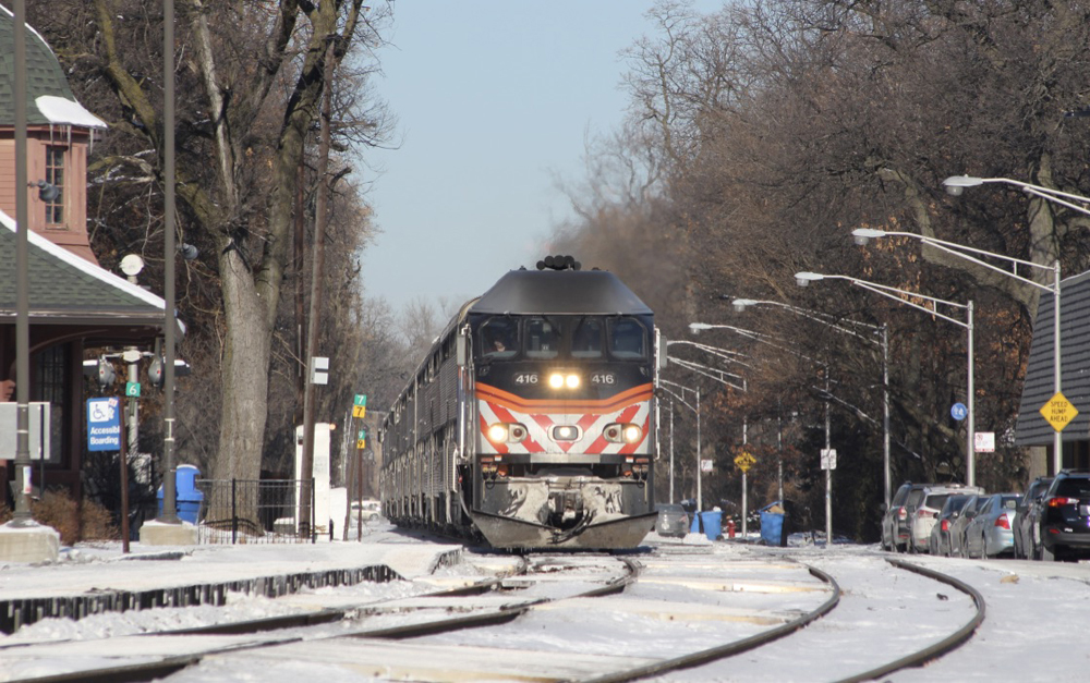 Commuter train led by locomotive with black, orange, and white nose arrives at station on sunny day with snow on the ground.