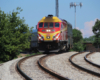 Red and yellow locomotive brings commuter train around sharp curve