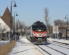 Train stops at station on cold, sunny day with snow covering the ground.