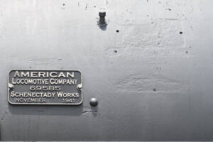 """Metal plate reading """"American Locomotive Company"""" with date and serial number; bolt holes nearby show former locations of earlier versions of plate."""