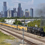Steam locomotive and diesel pulling yellow passenger train