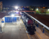 Big Boy steam locomotive rests on track at nighttime surrounded by lights.