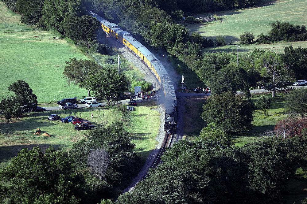 Big Boy locomotive moving over a rural grade crossing.