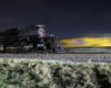 A yellow locomotive appears as a motion blur at night as the Big Boy steam locomotive is paused.