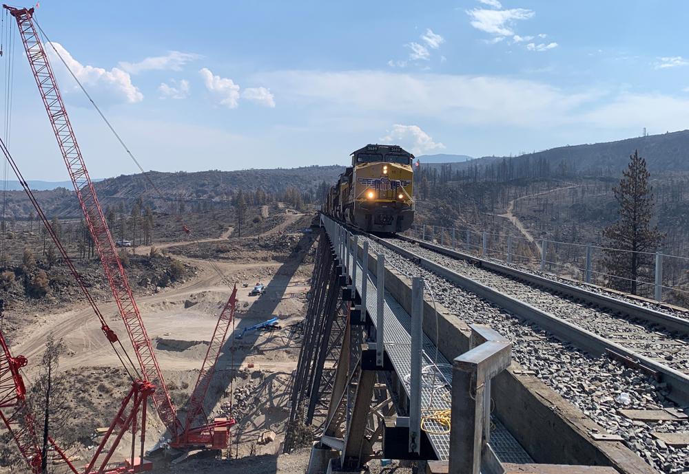 Train crossing bridge next to construction equipment