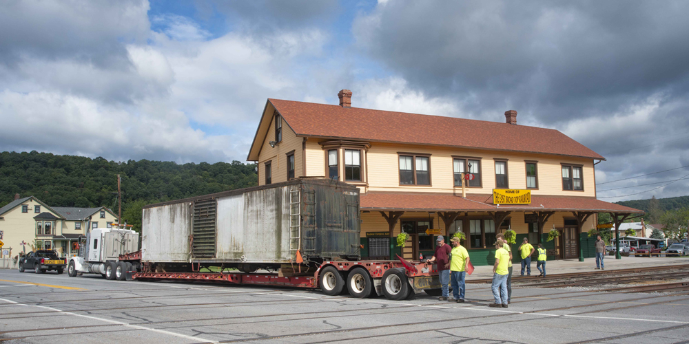 Boxcar on truck trailer next to station building