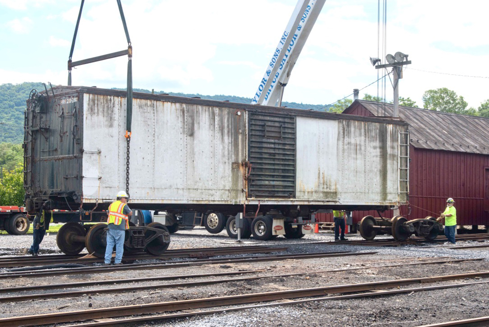 Boxcar being lowered by cranes