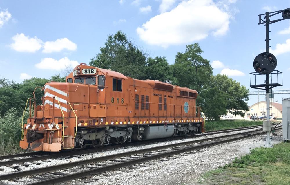 Orange locomotive next to color position signals