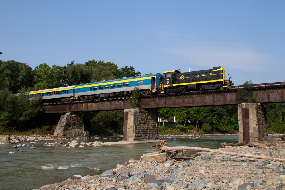 Black and yellow locomotive pulling passenger cars