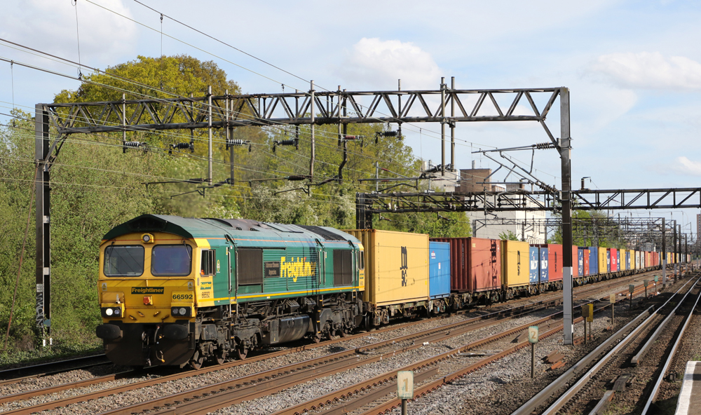 Green and yellow box-cab diesel pulling freight train