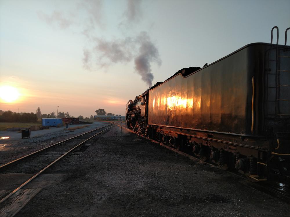 Rising sun reflecting on side of locomotive