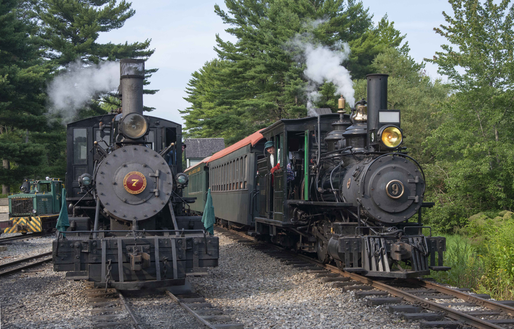 Two small locomotives under steam with trains