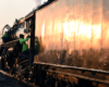 Close-up view of a steam locomotive tender reflecting low angle sunlight as a railroader climbs into a steam locomotive cab.