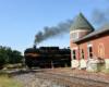 Steam locomotive nosing past old brick passenger station.