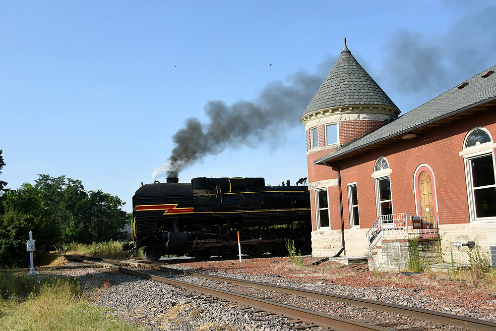 Steam locomotive noses past an old brick train station.