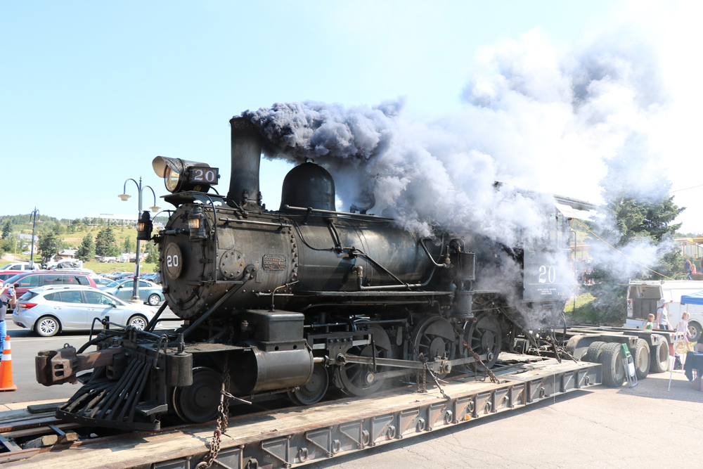 Smoke comes from stack of locomotive on trailer