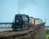 Large steam locomotive with train on long bridge seen with telephoto lens.