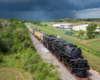 Large steam locomotive hauling train under clouded skies with a storm in the far distant background.