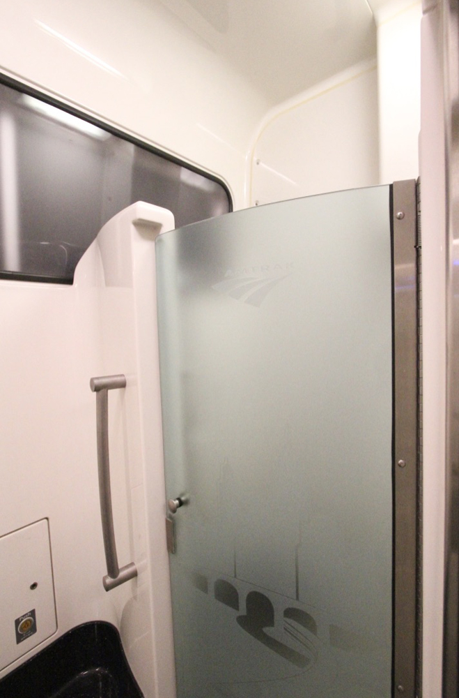 Shower on pasenger car with pink walls and smoked-glass door