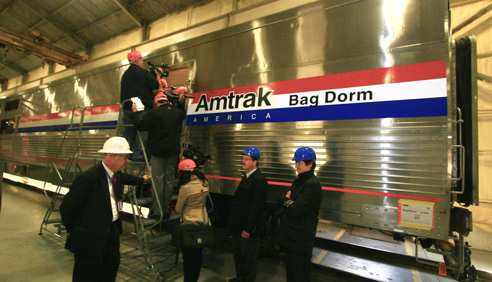 People in hard hats entering stainless steel passenger car