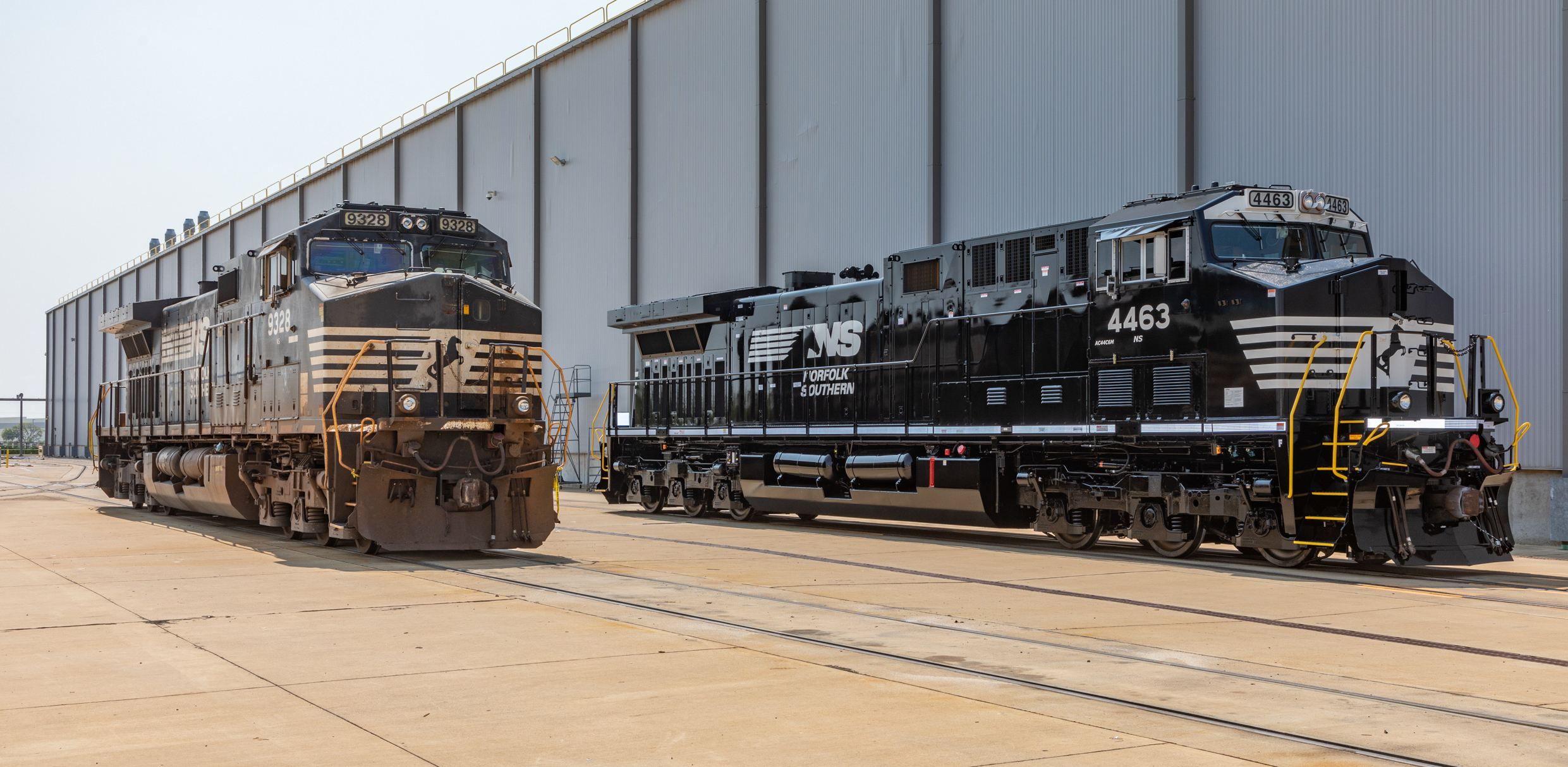 Two black locomotives, one weathered, the other new and shiny