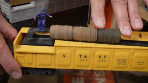 Close-up of yellow Lionel no. 3562 barrel car with barrels and worker.