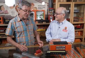 John Truckenbrod and Roger Carp with a small set of red wooden barrels.