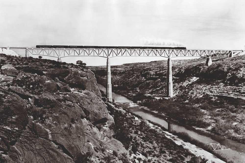 Steam-powered passenger train on deck truss bridge supported by concrete piers