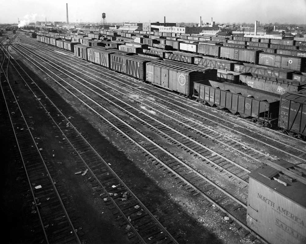 Freight cars line up in a rail yard seen from above